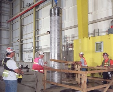 Workers handle an empty container, called a multi-canister overpack, used to store irradiated reactor fuel.